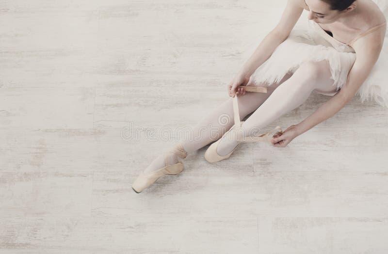 De ballerina zet op de schoenen van het pointeballet, bevallige benen stock afbeeldingen