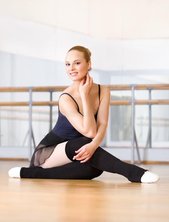 De balletdanser werkt zitting op de houten vloer uit stock afbeeldingen