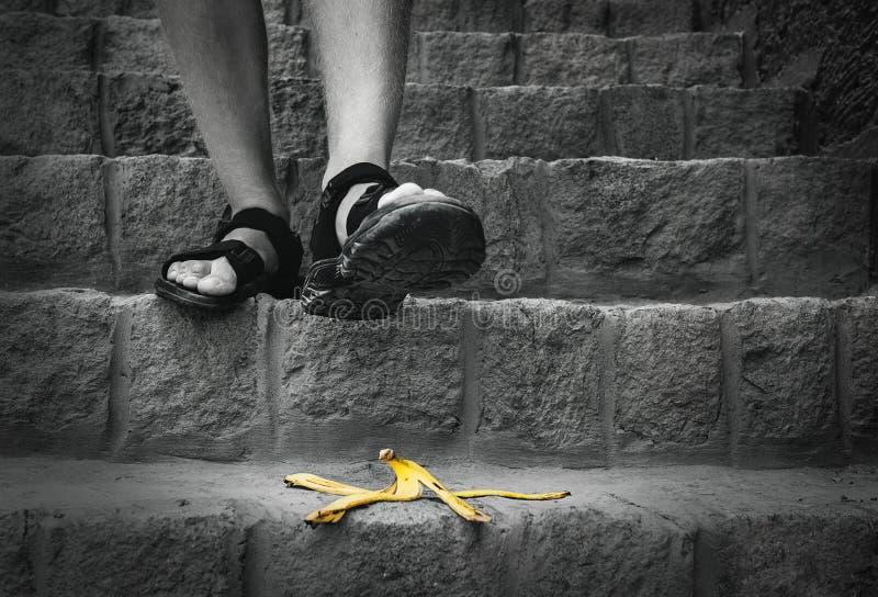 De banaan` s schil is op de treden - de reiziger kan stappen op het stock fotografie