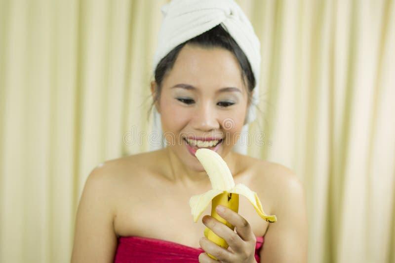 De banaan van de vrouwenholding de grappige acterenglimlach, droevig, draagt een rok om haar die borst na washaar te behandelen,  royalty-vrije stock foto's