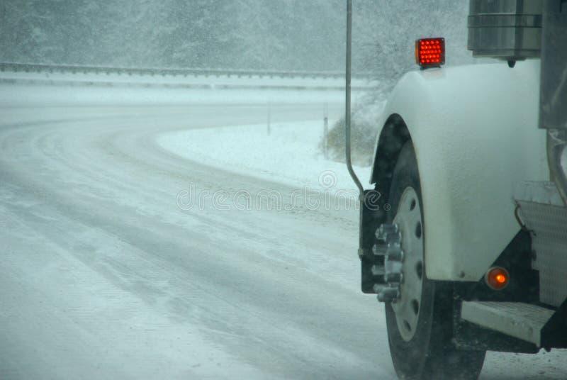De banden die van de vrachtwagen op weg tijdens sneeuwstorm spinnen stock afbeelding