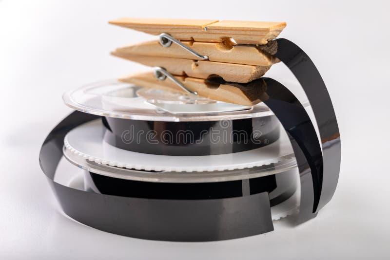 De banden met een videoopname worden vastgemaakt met een wasklem Het verbinden van en het herstellen van oude analoge opnamen stock foto