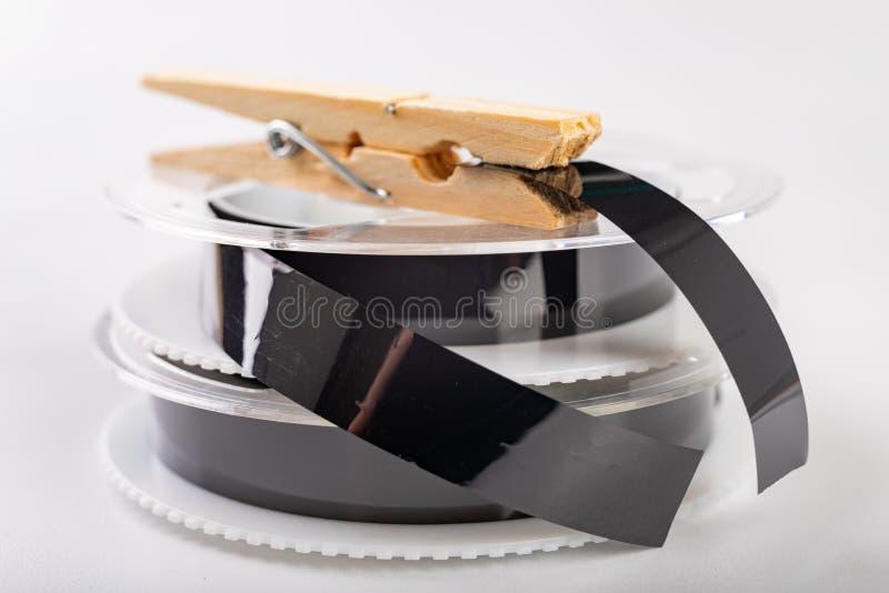 De banden met een videoopname worden vastgemaakt met een wasklem Het verbinden van en het herstellen van oude analoge opnamen stock afbeelding