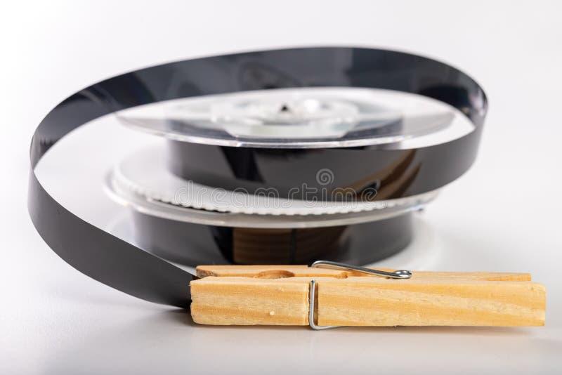 De banden met een videoopname worden vastgemaakt met een wasklem Het verbinden van en het herstellen van oude analoge opnamen stock afbeeldingen