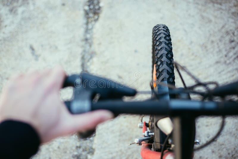 De banden van de bergfiets buiten, onscherp stuur, de zomerdag, stadsmobiliteit stock fotografie