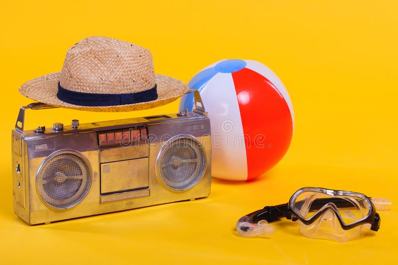 de bandrecorder, hoed, strandbal en snorkelt met scuba-uitrustingsmasker op geel wordt geïsoleerd die royalty-vrije stock afbeeldingen