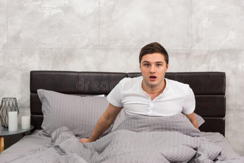 De bang gemaakte mens ontwaakte van een nachtmerrie, zittend in bed royalty-vrije stock fotografie