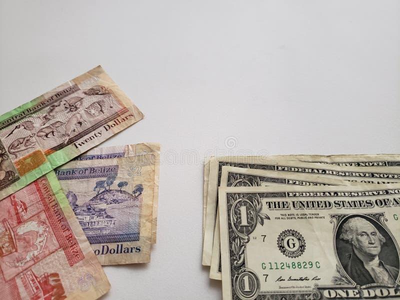 De bankbiljetten van Belize van verschillende benamingen en Amerikaanse dollarrekeningen op witte achtergrond stock afbeeldingen