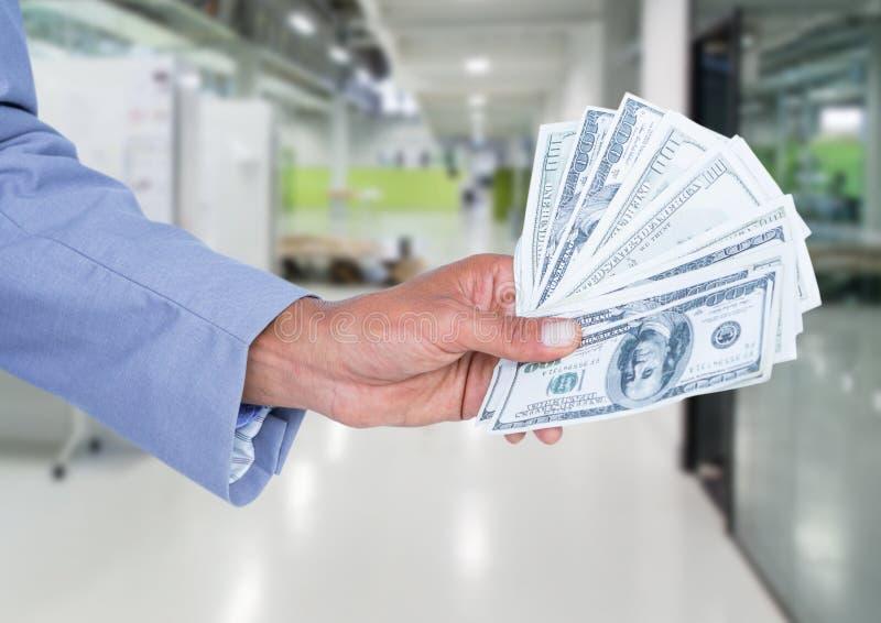 De bankbiljetten van de de holdingsdollar van de zakenmanhand stock foto
