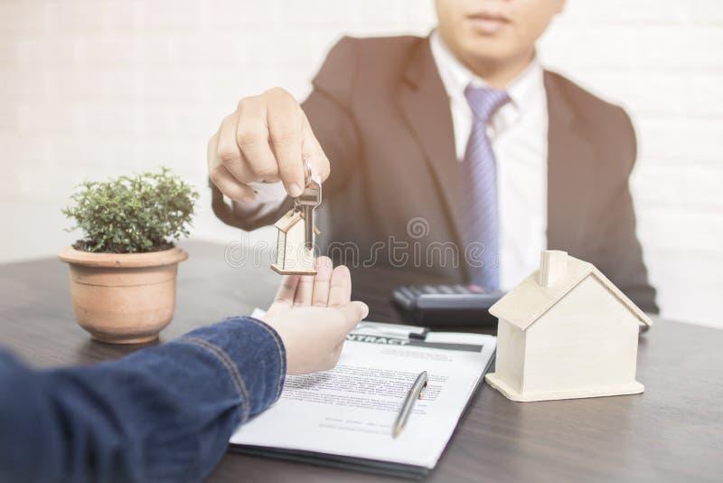 De bankier geeft huissleutel aan koper na het beëindigen van aankoophuis royalty-vrije stock foto