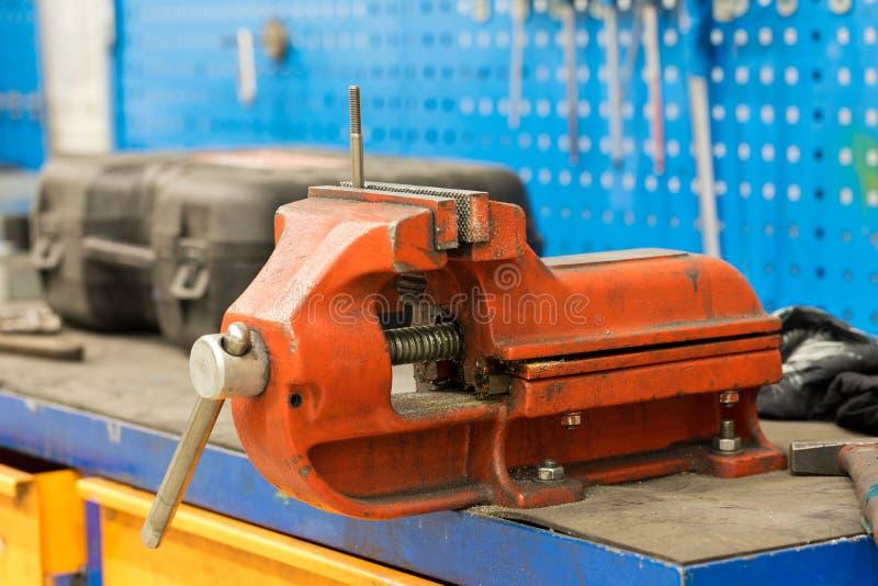 De bankschroefmachine van Engineerin bijlage aan een werkbank stock fotografie