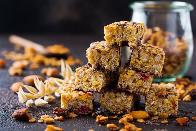De bar van graangewassengranola met noten, vruchten en bessen op donkere steenlijst De staaf van Granola Gezonde Snack stock foto