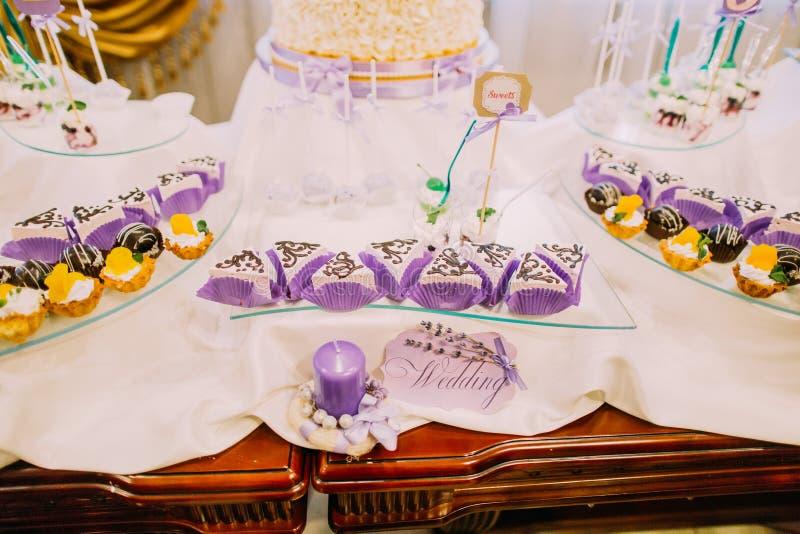 De bar van het huwelijksdessert Close-upmening van de zoete die cakes op de lijst met huwelijkstekens en kaarsen wordt verfraaid stock foto's