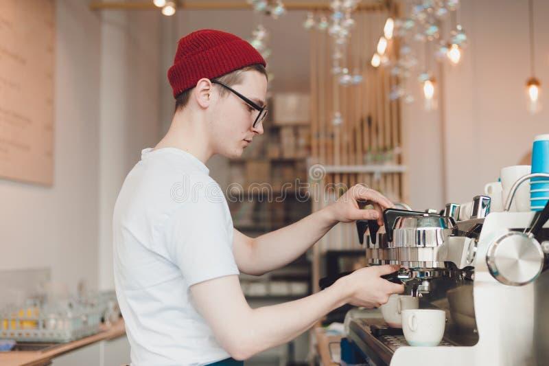 De Baristatribunes achter de koffiemachine en maakt koffie stock foto