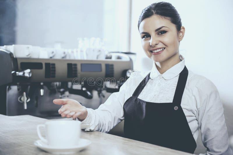 De Baristavrouw biedt cappuccino in koffie aan stock fotografie