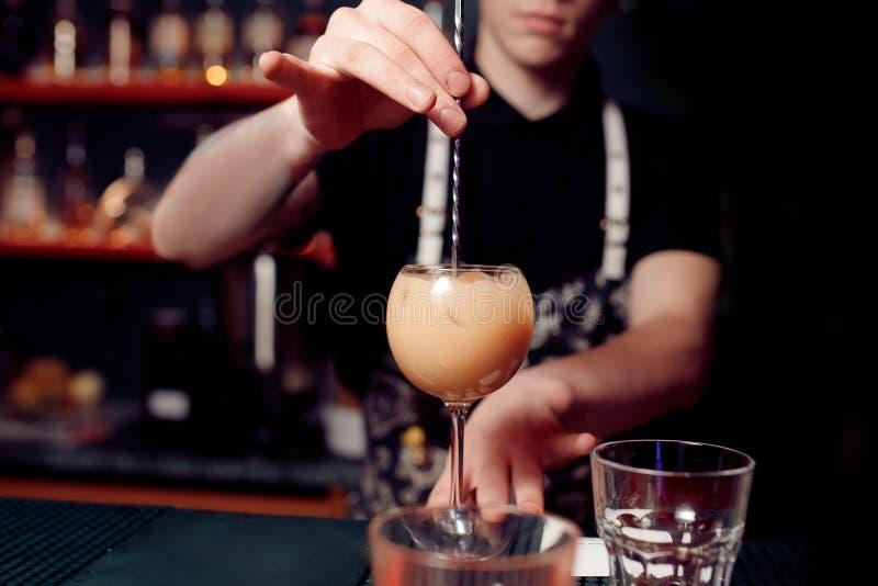 De barman bereidt cocktail in transparant glas op bar met alcohol voor royalty-vrije stock foto's