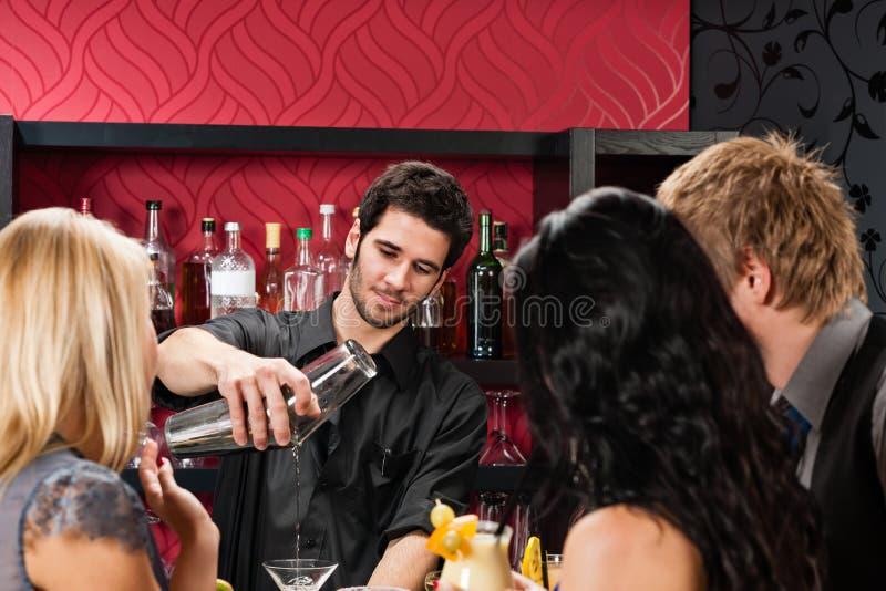 De barman bereidt cocktailvrienden voor die bij staaf drinken stock afbeeldingen