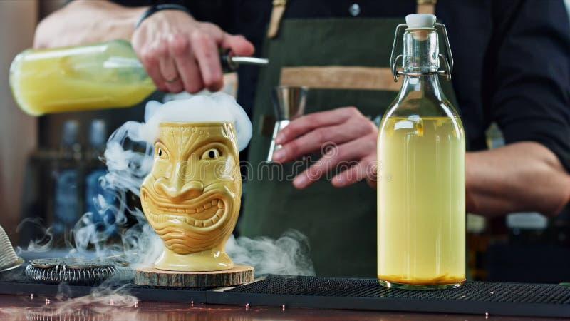 De barman bereidt een cocktail bij de bar voor stock afbeeldingen