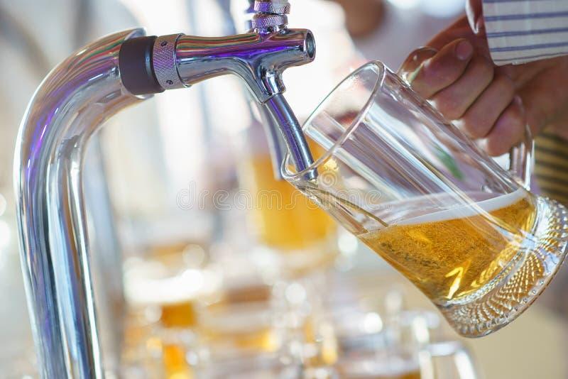De barman giet een licht schuimend bier in een grote mok tijdens de Oktoberfest-partij stock afbeelding