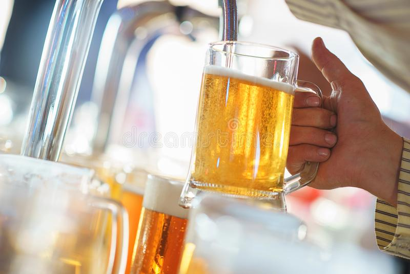 De barman giet een licht schuimend bier in een grote mok tijdens de Oktoberfest-partij stock foto