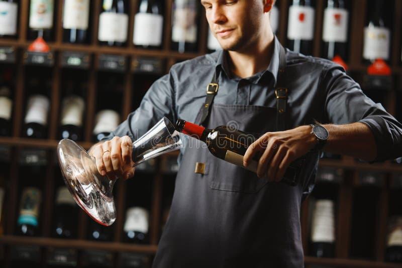 De barman giet rode wijn in transparant schip in kelder stock foto's