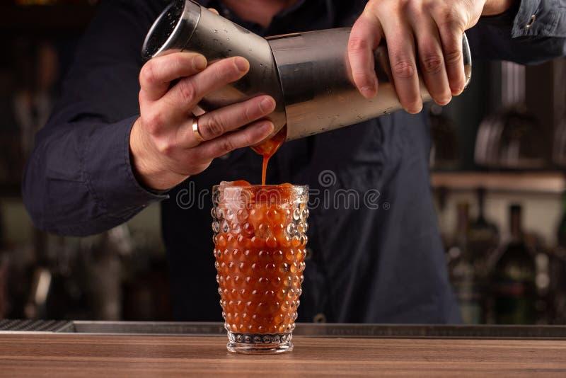De barman giet tomaat rood sap van de schudbeker, makend een cocktail, drank stock foto's