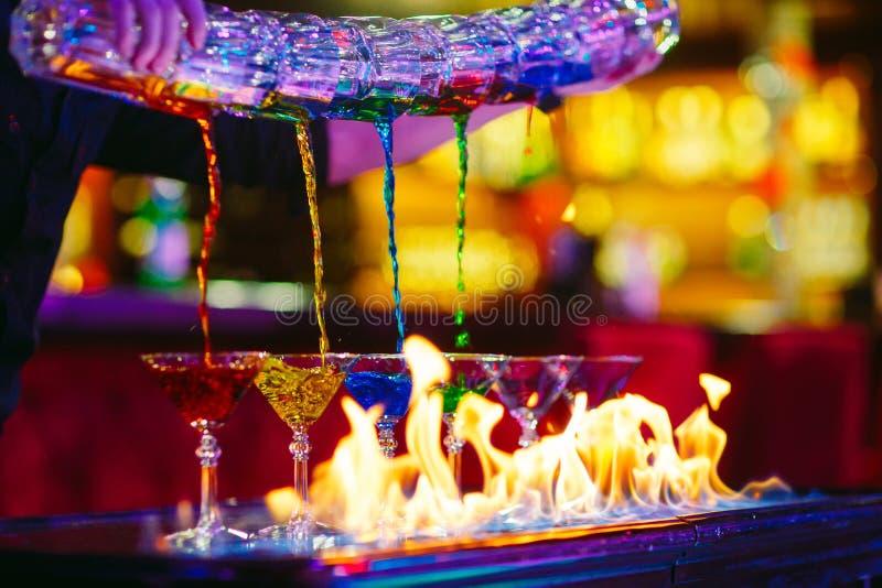 De barman toont De barman giet alcoholische kleurrijke cocktails royalty-vrije stock foto's