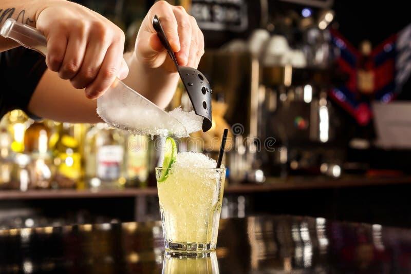 De barman verfraait cocktail met verpletterd ijs bij bar stock foto's