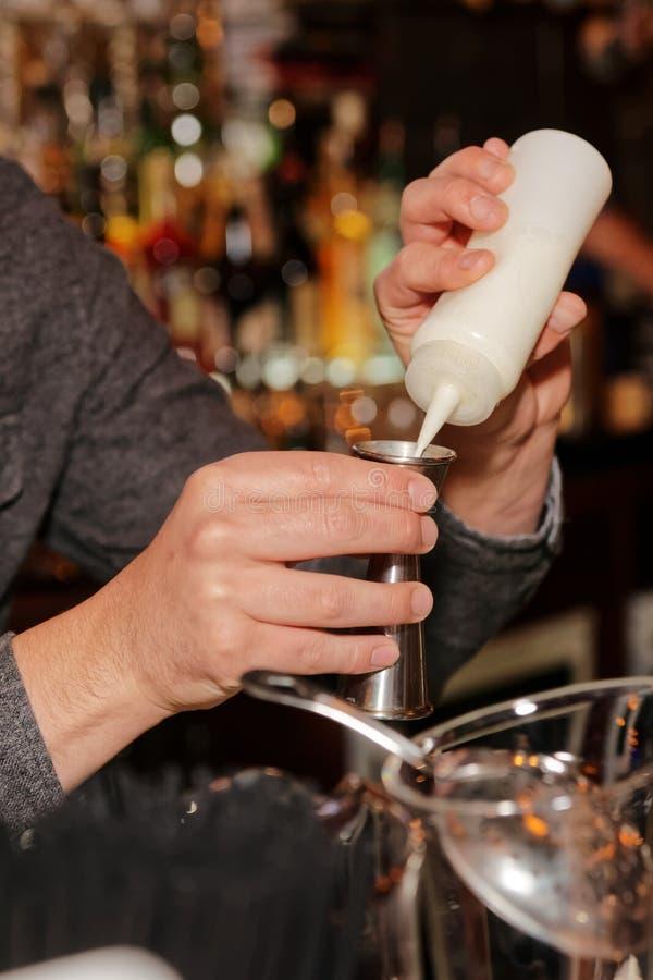 De barman voegt geheim ingrediënt in cocktail toe stock fotografie