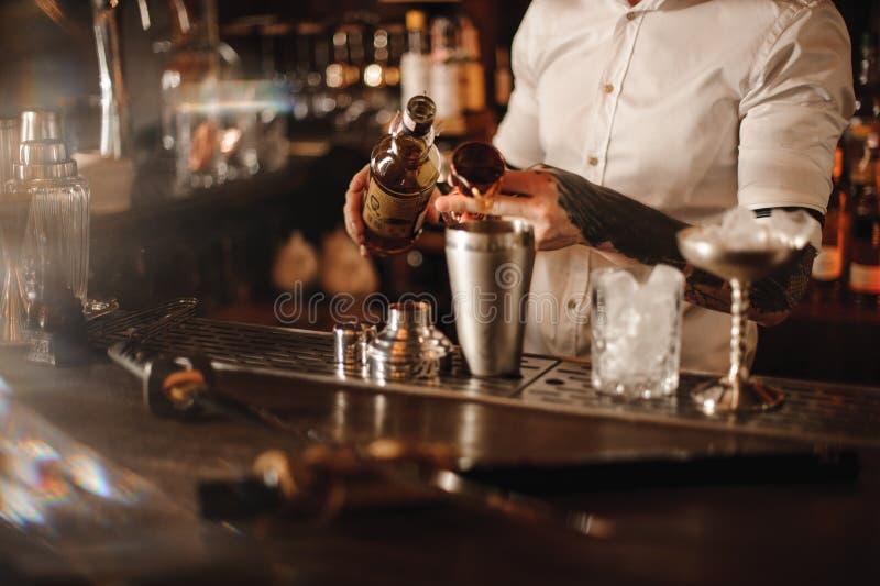 De barman voegt ingrediënt in schudbeker bij barteller toe royalty-vrije stock afbeeldingen