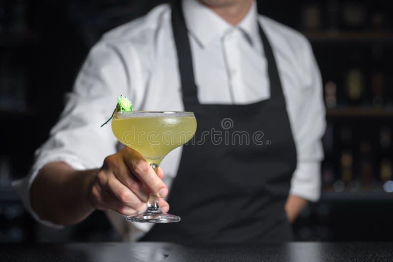 De barmannen houdt Cezaritz-cocktail met bloem in glas CH wordt verfraaid die stock foto