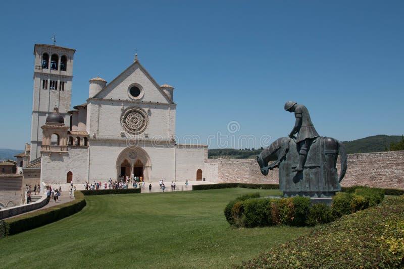 De Basiliek van St Francis San Francesco en het standbeeld van St Francis op een paard, Assisi, Italië stock afbeelding