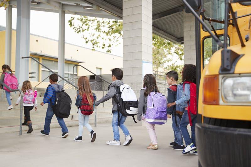 De basisschooljonge geitjes komen bij school van de schoolbus aan stock fotografie