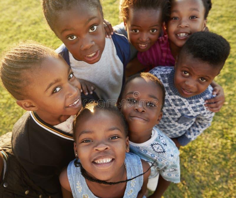 De basisschooljonge geitjes op een gebied bekijken omhoog camera het glimlachen royalty-vrije stock afbeelding