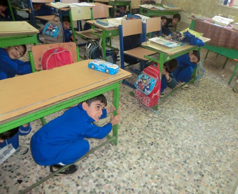 De basisschooljongens van het aardbevingsmanoeuvre Aardbevingsmanoeuvre in basisschooljongens stock foto's