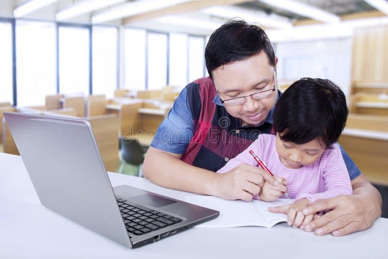 De basisschoolleraar helpt zijn student royalty-vrije stock foto