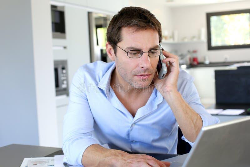 De beambte die van het huis op de telefoon spreekt stock foto