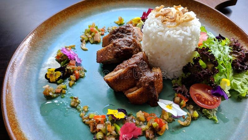 De Bebek areh sambal matah is Indonesisch traditioneel voedsel, smakelijk die eendvlees met verse matal saus wordt gecombineerd stock foto's