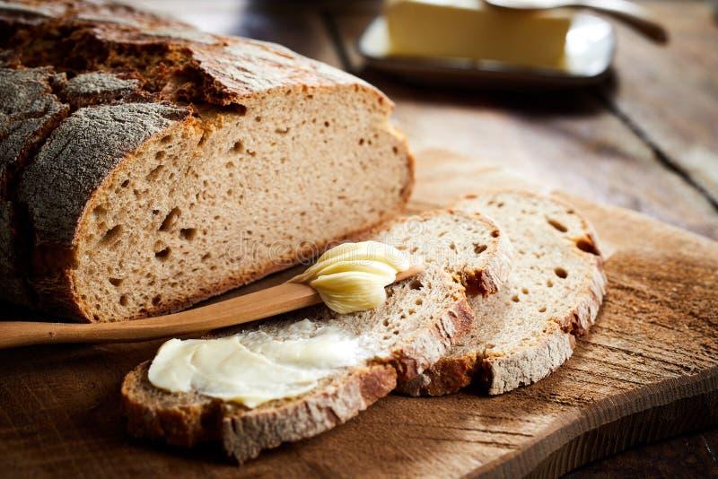 De beboterde plak van vers bakt roggebrood stock afbeelding