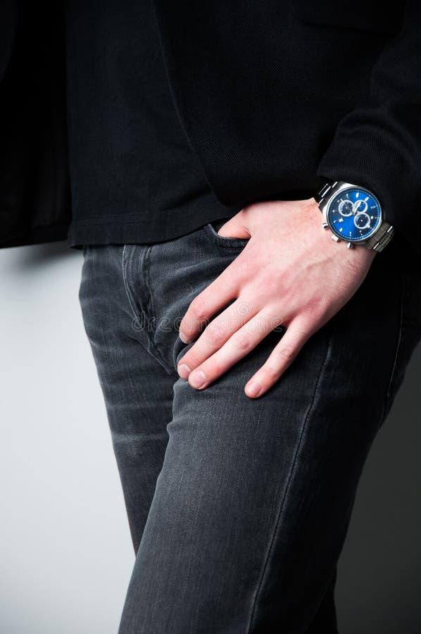 De bebouwde hoofdmens in zwarte blazer met dient de zak van jeans in stock foto