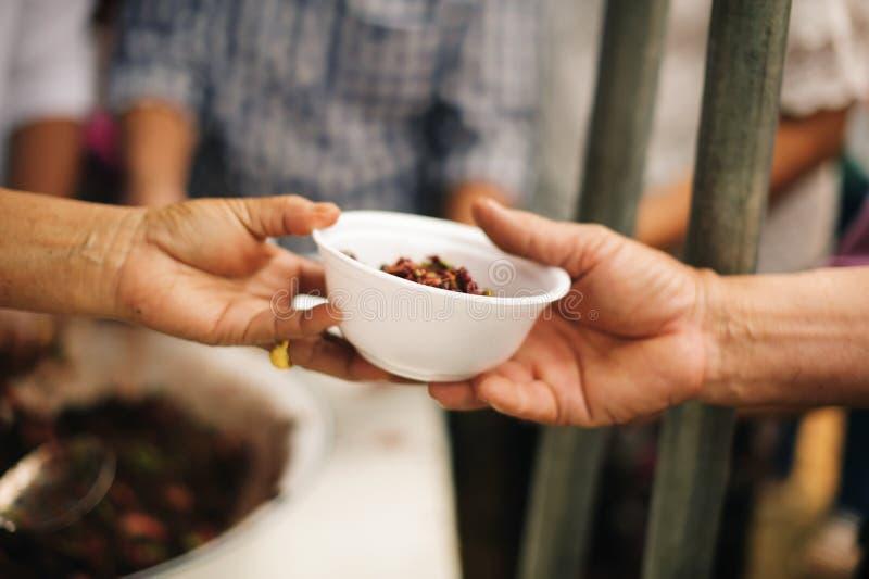 De bedelaar bedelt voedsel van donors: Gevend voor mede menselijke wezens in de maatschappij door voedsel te geven, die zonder Ho royalty-vrije stock foto