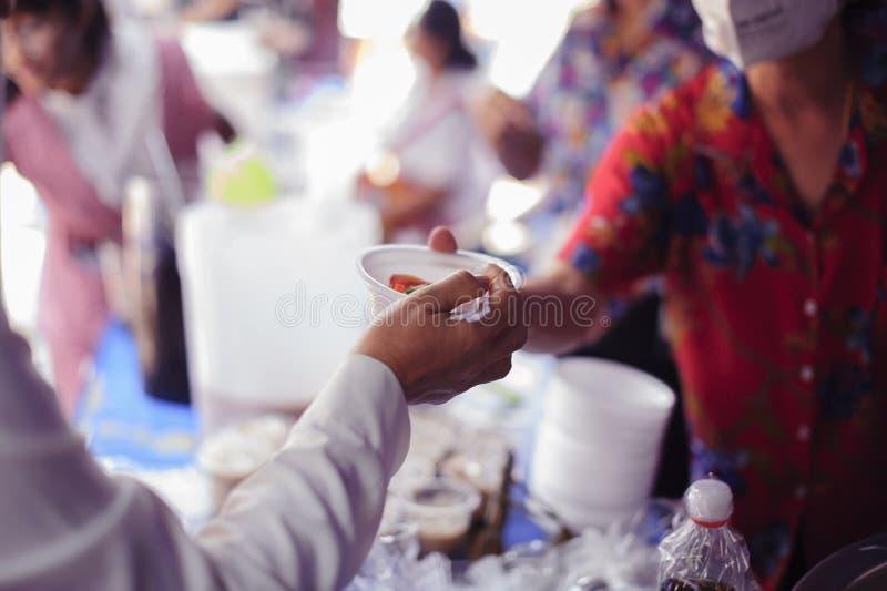 De bedelaar bedelt voedsel van donors: Gevend voor mede menselijke wezens in de maatschappij door voedsel te geven, die zonder Ho royalty-vrije stock afbeelding