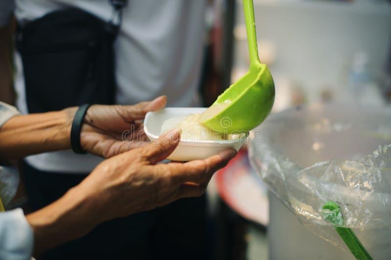 De bedelaar bedelt voedsel van donors: Gevend voor mede menselijke wezens in de maatschappij door voedsel te geven, die zonder Ho stock foto's
