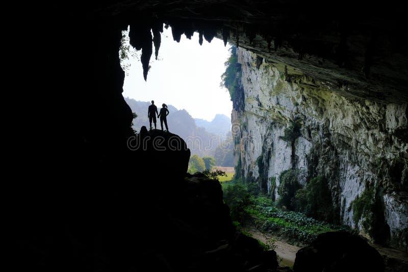 De bedelaars zijn Meren/Vietnam, 03/11/2017: Silhouetten van twee mensen die zich in een rotsachtige dagzomende aardlaag binnen e stock foto