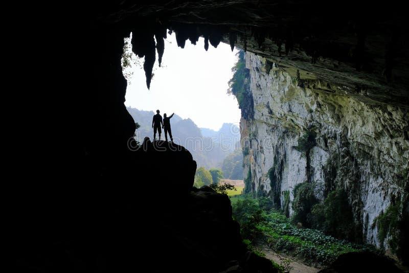 De bedelaars zijn Meren/Vietnam, 03/11/2017: Silhouetten van twee mensen die zich in een rotsachtige dagzomende aardlaag binnen e royalty-vrije stock foto's