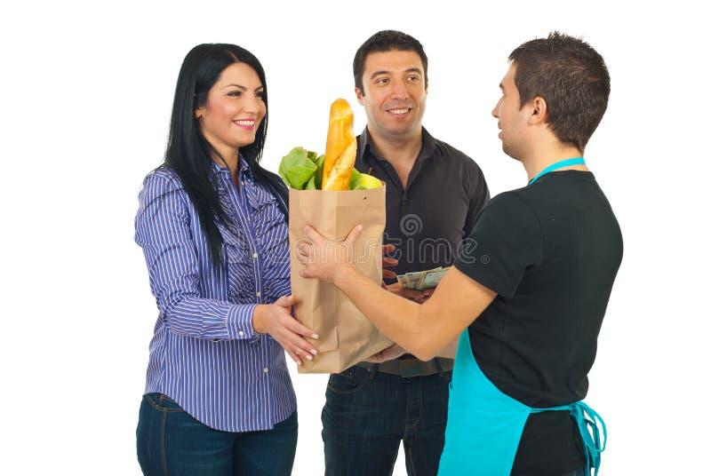 De bediende die van de kruidenierswinkel zak geeft aan paar royalty-vrije stock afbeelding
