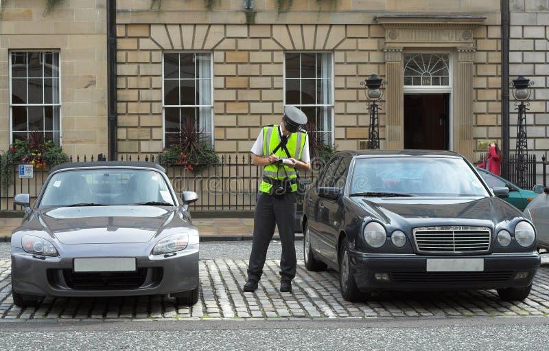 De bediende van het parkeren, verkeershoofd, dat kaartjes fijn mandaat krijgt stock afbeeldingen