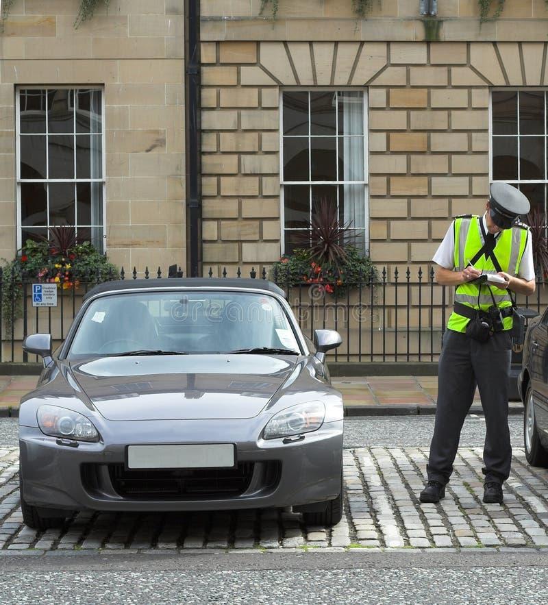 De bediende van het parkeren, verkeershoofd, dat kaartjes fijn mandaat krijgt stock foto