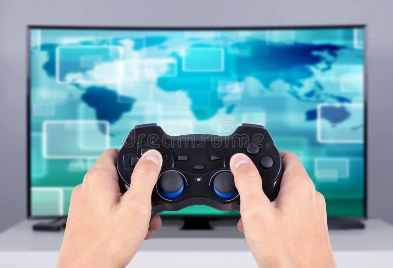 De bedieningshendel van de handholding aan het spelen videospelletje op TV stock foto's