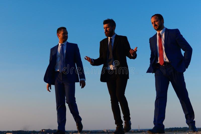 De bedrijfleiders nemen een gang op de achtergrond van de zonsonderganghemel royalty-vrije stock afbeelding